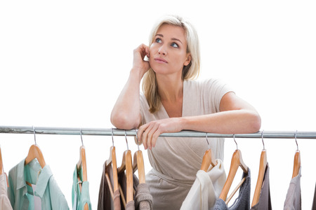 clothes rail: Pretty blonde looking through clothes rail on white background