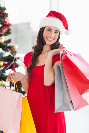 Smiling brunette in red dress holding shopping bags at home in the living room photo