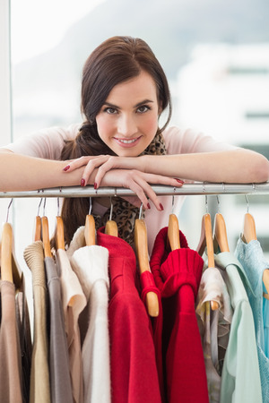 clothes rail: Pretty brunette smiling at camera by clothes rail at clothes store Stock Photo