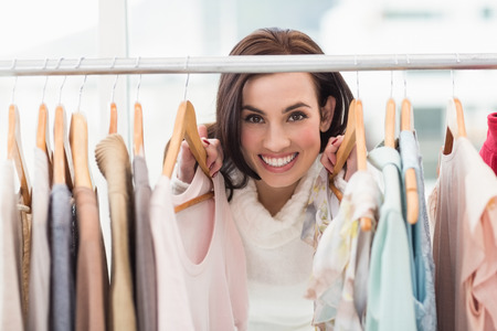 clothes rail: Beauty brunette smiling at camera by clothes rail at clothes store