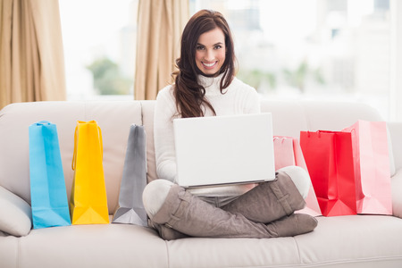 Brunette shopping online with laptop on the couch at home in the living room