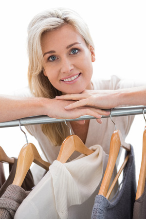 clothes rail: Pretty blonde smiling at camera by clothes rail on white background Stock Photo