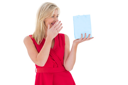 Stylish blonde in red dress holding gift bag on white background photo