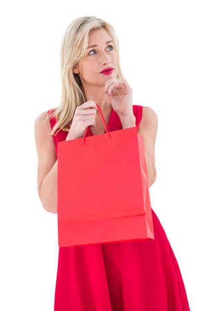 Stylish blonde in red dress opening gift bag on white background photo