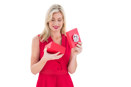 opening gift: Stylish blonde in red dress opening gift box on white background