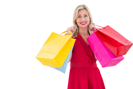 evening wear: Stylish blonde in red dress holding shopping bags on white background