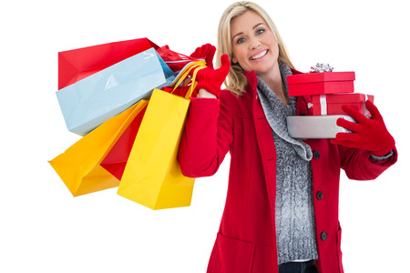 Festive blonde holding many gifts on white background photo