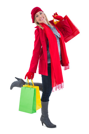Happy blonde in winter clothes holding shopping bags on white background photo