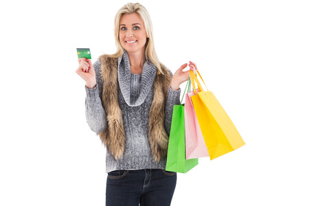 Blonde in winter clothes holding shopping bags on white background photo
