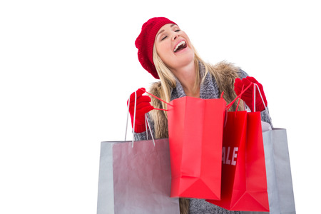 Blonde in winter clothes with shopping bags on white background photo