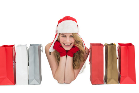 Smiling woman lying between shopping bags on white background photo