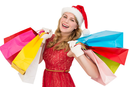 Excited blonde in santa hat holding shopping bags on white background photo