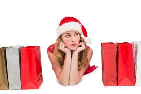 female christmas: Thoughtful woman lying between shopping bags on white background