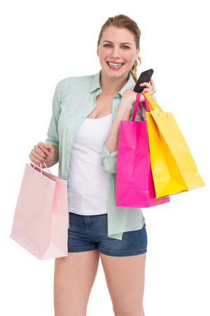 Pretty blonde smiling at camera holding shopping bags on white background photo