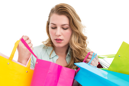 Blonde woman opening gift bag and looking on it on white background photo