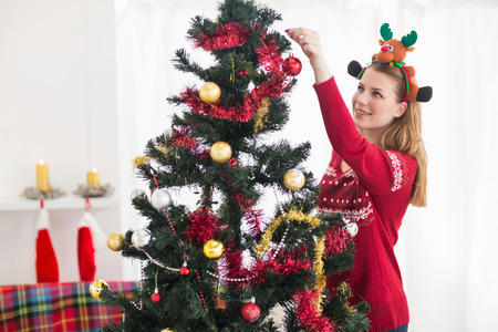 home decorating: Young woman decorating a Christmas tree at home in the living room