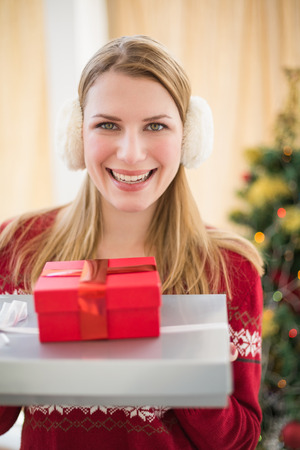 Earmuffs: Smiling blonde wearing earmuffs while holding gifts at home in the living room Stock Photo