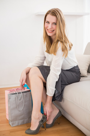 removing: Smiling woman sitting on couch taking off her shoes at home in the living room