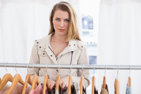 clothes rail: Pretty blonde looking at camera by clothes rail in the store