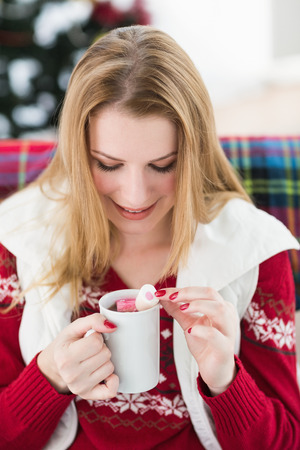 Happy blonde in winter clothes holding mug at home in the living room photo