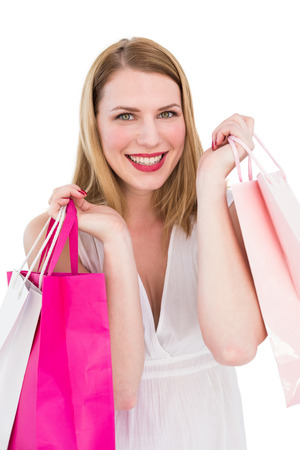 Cheerful blonde woman holding shopping bags on white background photo