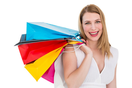 Pretty woman carrying shopping bags over her shoulder on white background photo
