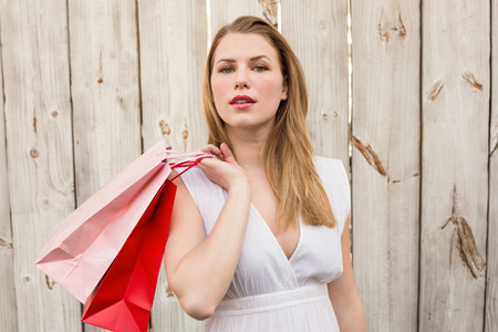 Pretty woman carrying shopping bags over her shoulder in front of a wooden wall photo