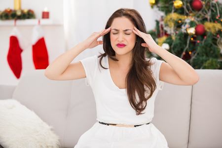 pounding head: Brunette getting a headache on christmas day at home in the living room