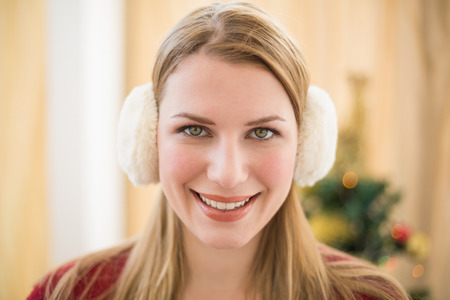 Earmuffs: Portrait of a smiling blonde wearing earmuffs at home in the living room