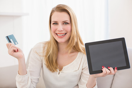 Pretty blonde shopping online with tablet at home in the living room photo