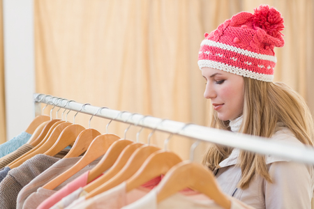 clothes rail: Close up of a pretty blonde looking at clothes on rail in the store