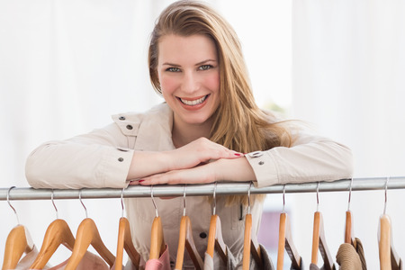 clothes rail: Pretty blonde smiling at camera by clothes rail in the store