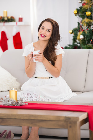 Smiling brunette enjoying a hot beverage at christmas at home in the living room photo