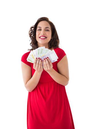 Stylish brunette in red dress holding cash on white background photo
