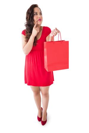 Brunette thinking and holding shopping bag on white background photo