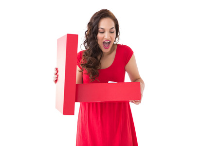 Astonished brunette holding a box on white background photo