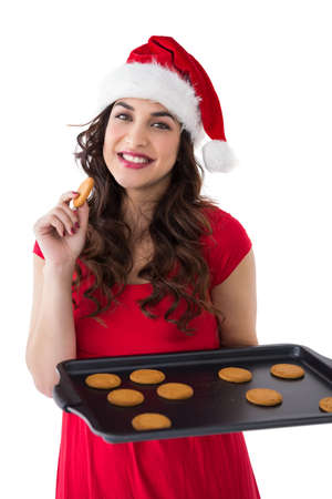 Festive brunette eating hot cookies on white background photo