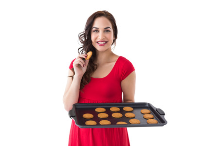 Happy brunette eating hot cookies on white background photo