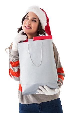 Thoughtful brunette holding shopping bag full of gifts on white background photo