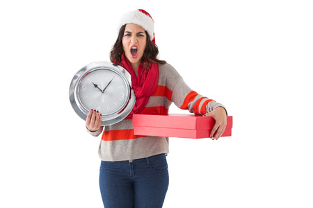 Surprised brunette holding a clock and gift on white background photo