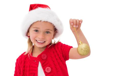wearing santa hat: Cute little girl wearing santa hat holding bauble on white background
