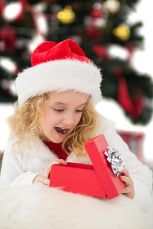 Festive little girl looking at gift on white background photo
