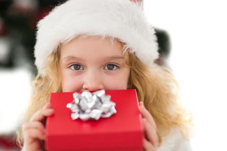 Festive little girl holding a gift on white background photo