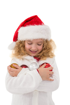 Festive little girl holding baubles on white background photo