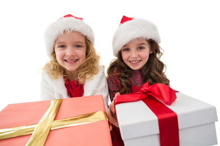 Festive little girls smiling at camera holding gifts on white background photo