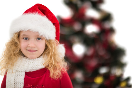 Festive little girl in santa hat and scarf on white background photo