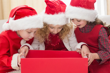 Festive little siblings looking at gift at home in the living room photo