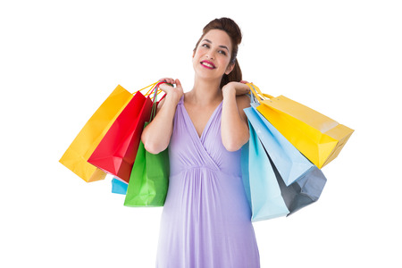 Thoughtful brunette holding shopping bags on white background photo