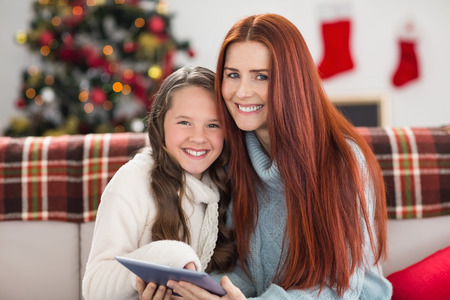 Festive mother and daughter using tablet on the couch at home in the living room photo