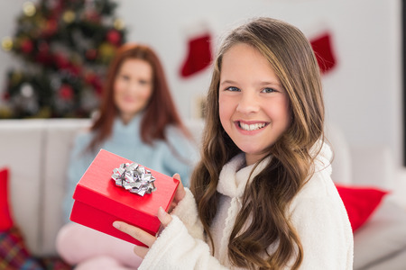 Festive little girl holding a gift at home in the living room photo